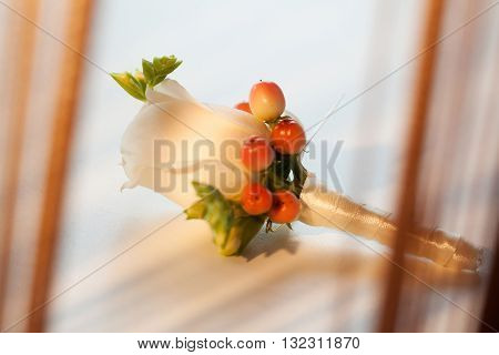 Men's wedding buttonhole with white rose and berries