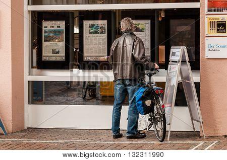 FREIBUG IM BREISGAU GERMANY - OCTOER 07 2011: Man reading digital newspaper in the window of the Badische Zeitung newsaper in Freiburg Germany.