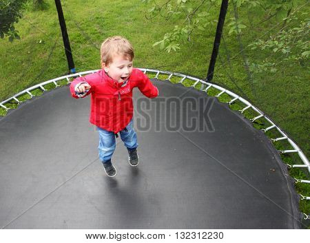 Funny kid playing and jumping on a outdoor trampoline. Children enjoying life. Vacations on countryside. Healthy lifestyle.