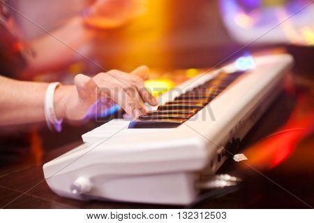 DJ plays in the club on a synthesizer.