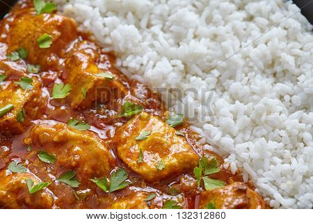 Chicken tikka masala close up texture, traditional Asian spicy meat food with rice and parsley