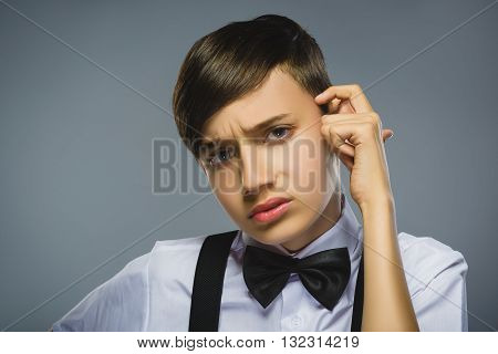 Close up Thoughtful Young Boy Looking forward with Hand on the Face Against Gray Background with Copy Space.