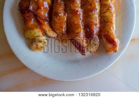 Bacon wrapped chicken tenders in honey glaze arranged on plate