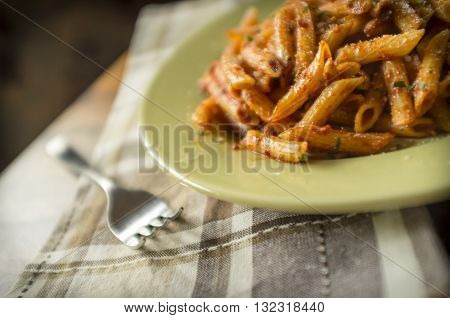 Penne alla vodka in rustic kitchen setting on green plate