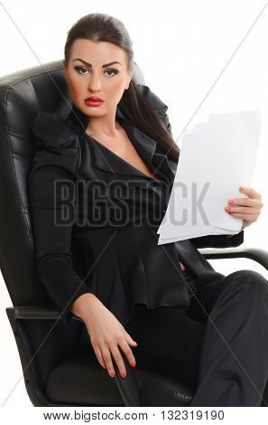 Portrait of a confident young woman sitting in an armchair  with documents