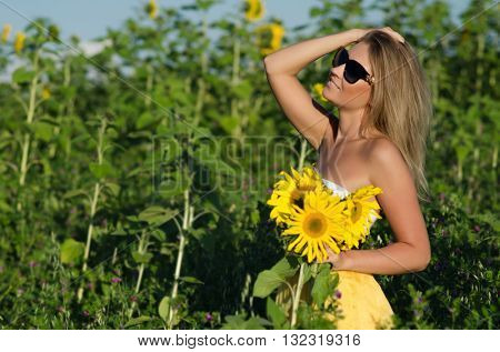 Portrait of a beautiful young blonde woman ion a background field of sunflowers