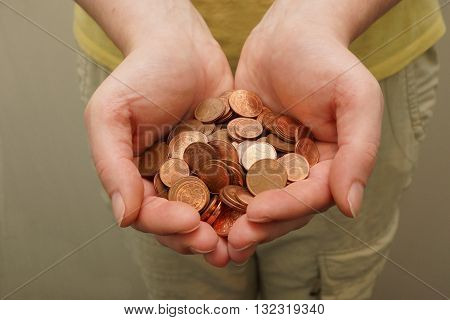 Many euro cent coins in woman hand