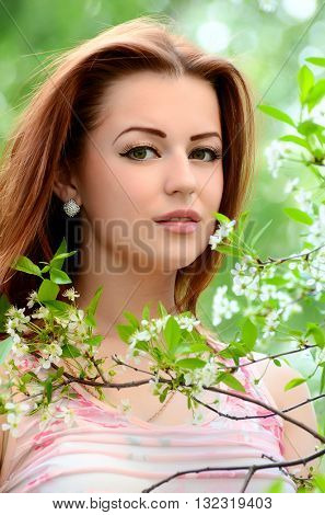 The beautiful woman in flowers of cherry