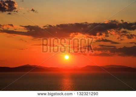 Bright vivid sundown in cloudy sky over beautiful still water and mountains