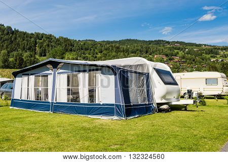 Modern caravan with caravan tent at campsite in Norway on a sunny summer day.
