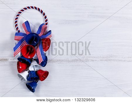 Colorful bells and ribbons on rustic white wooden boards. Fourth of July holiday concept for United States of America.