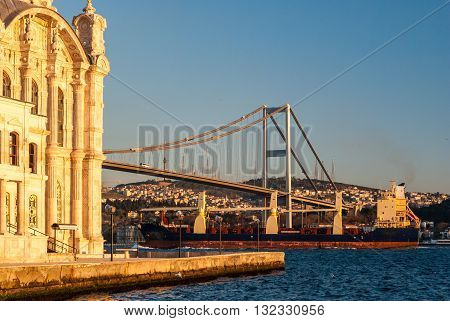 The Ortakoy Mosque in Istanbul with the bridge across the Bosphorus and a containership in the background