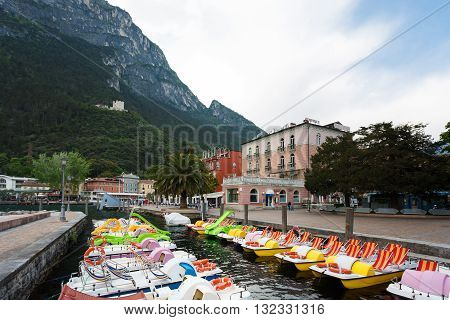 Riva del Garda Italy - May 03 2016: Recreational catamarans in a marina on the waterfront of little resort town located in the Northern part of Lake Garda