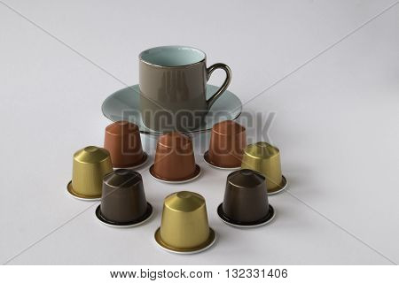 Smart espresso cup and saucer with selection of coffee pods on white background