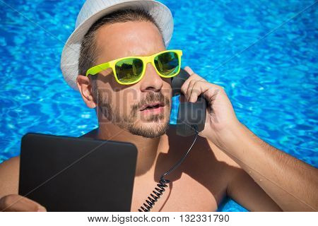 Portrait of a handsome man making a call in the swimming pool by using digital tablet device and retro styled handset. Communication and summer vacation concept.