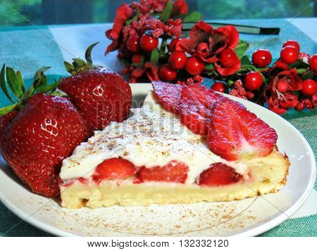 A piece of fresh homemade strawberry cake lying on a plate with a large fresh strawberries