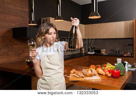 Beautiful young woman with a bottle of wine in her hands