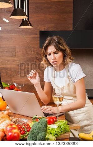 Young woman in the kitchen with laptop