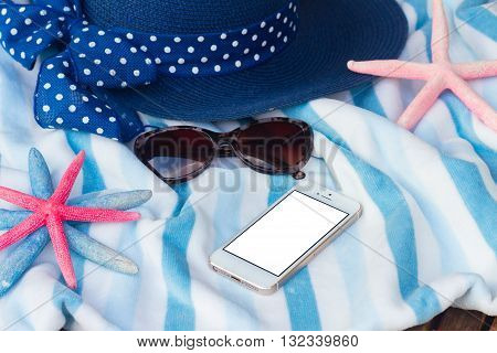 summer beach towel, starfish, sunglasses and hat, copy space on phone with blank screen