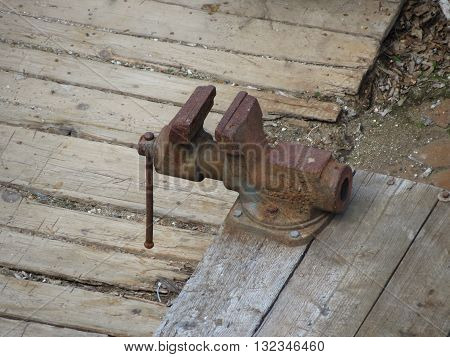 Forged steel bench vise old and rusted on a wooden table