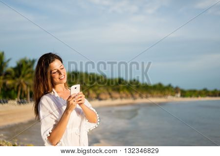 Happy woman on tropical summer vacation texting on smartphone towards the sea. Female tourist messaging on travel to Riviera Maya Mexico.