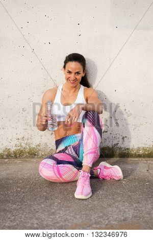 Fit muscular woman taking a workout rest for drinking water. Female strong athlete resting after exercising or running. Spring fashion sportswear.