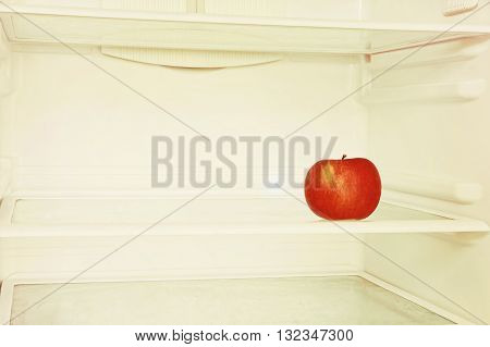 Single red apple in domestic refrigerator taken closeup. Toned image.