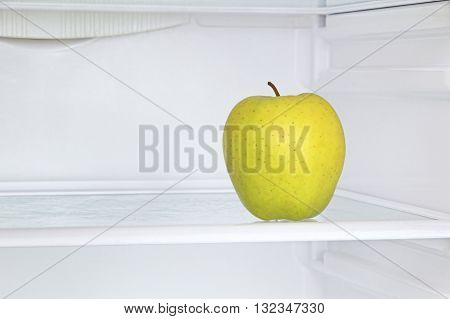 Lifestyle concept.Ripe yellow apple in domestic refrigerator taken closeup.