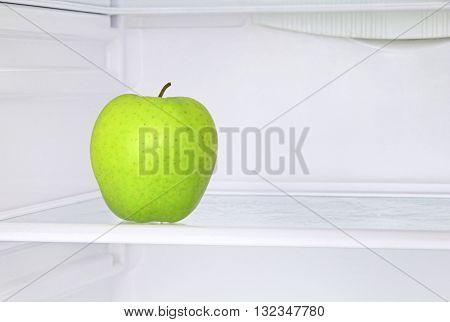 Lifestyle concept.Ripe green apple in domestic refrigerator taken closeup.