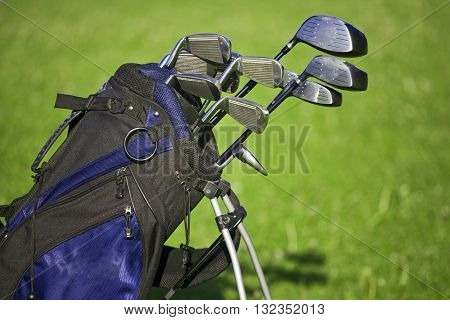 Golf clubs set in bag with golf field in background