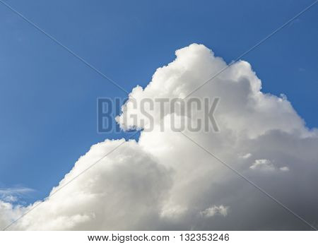 White Cumulus Clouds And Grey Storm Clouds Gathering On Blue Sky