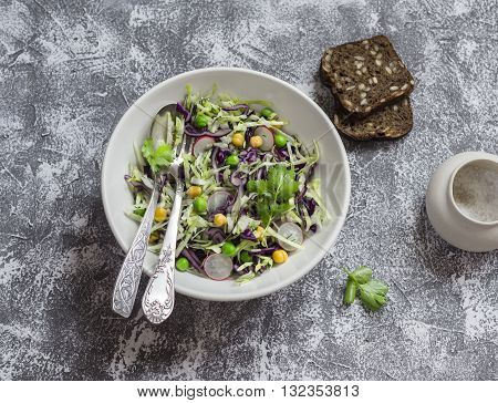 Fresh vegetable salad with white and red cabbage cucumber radish and cilantro in a ceramic dish on a stone texture. Healthy vegetarian food.