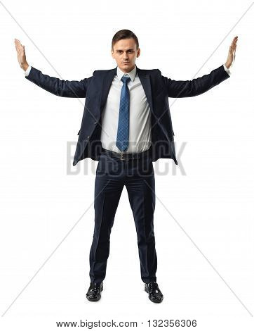 Businessman stands pushing invisible walls by his hands. Cutout portrait. Faith in his own strength. Business staff. To push the boundaries of the possible. Office clothes. Believe in yourself.  Dress code. Presentable appearance.