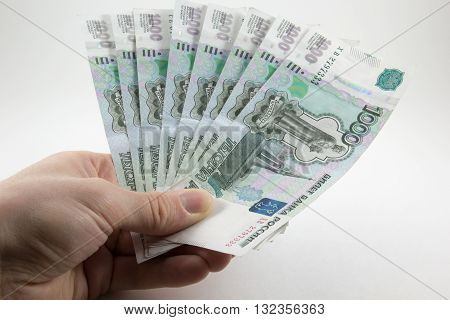 Hand with Russian rubles on a white background