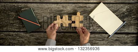 Top view of male hands assembling two wooden puzzle pieces with notebook and notepad pen and pencil lying on textured wooden desk panoramic image.