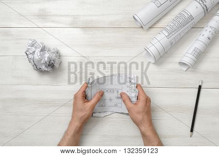 Masculine hands tearing a bad architect drawing to the pieces. Nervous condition. Workplace of architect or constructor. Anger sign. Worry process. Engineering work. Construction and architecture. Architect drawing. Draft.