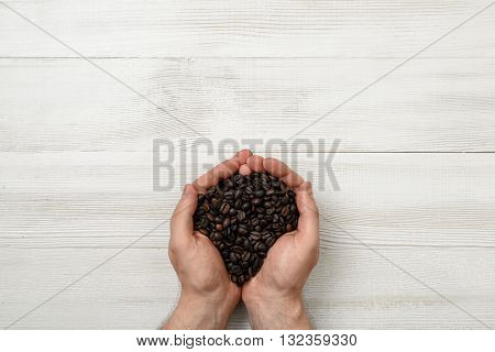 Close-up hands of man holding a handful of coffee beans. Top view composition. Workplace coffee maker. Top view. Coffee house. Uplifting mood. Coffee break.