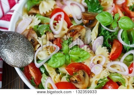 Warm salad of Farfalle with mushrooms and tomatoes in white plate on the table. Mediterranean cuisine