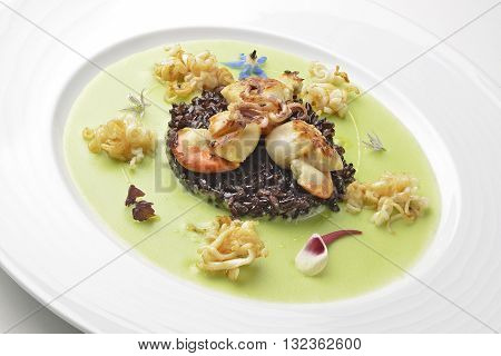 Appetizer of braised scallops and black rice on pea cream