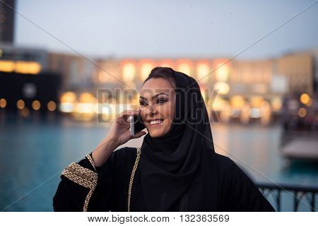 Young arabic woman talking on a mobile phone in the city.