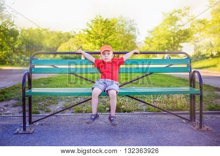 little boy sitting on a bench alone. the little boy opened his arms on the bench as if he were hugging their invisible parents