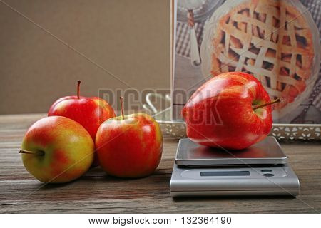 Apples with digital kitchen scales on wooden table. Cooking apple cake concept