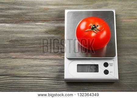 Tomato with digital kitchen scales on wooden background