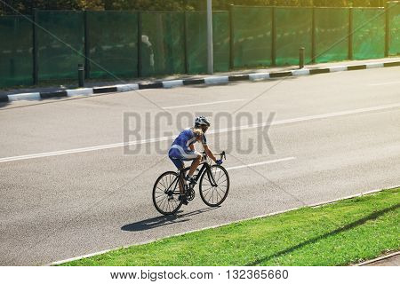 Cycling on the sunny road. Sport bicycle. Woman cycling on countryside summer road or highway. Training for triathlon or cycling competition. Highway cycling, evening light