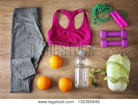 Sport equipment with female clothing and vegetables on wooden background