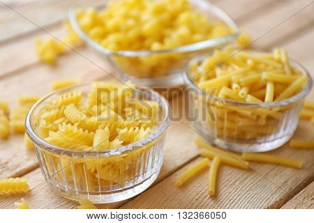 Fusilli pasta in glass bowl on wooden table