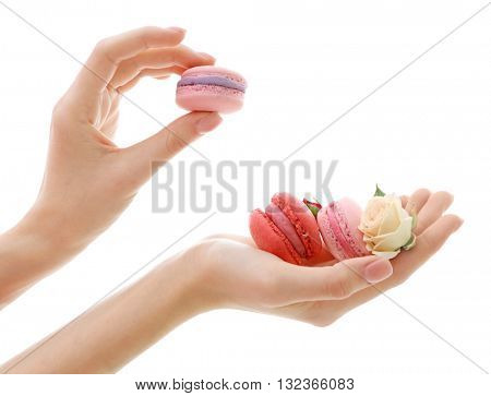 Female hands holding macaroons isolated on white