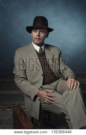 Fashionable Retro 1940 Business Man With Hat Sitting On Chair In Room.