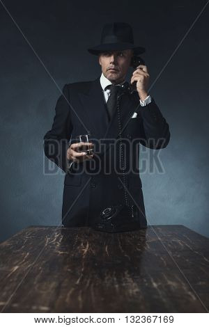 Retro 1940 Businessman On The Phone With Glass Of Whiskey. Standing Behind Wooden Table.