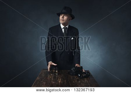 Vintage 1940 Businessman Grabbing Whiskey After Calling. Standing Behind Wooden Table.